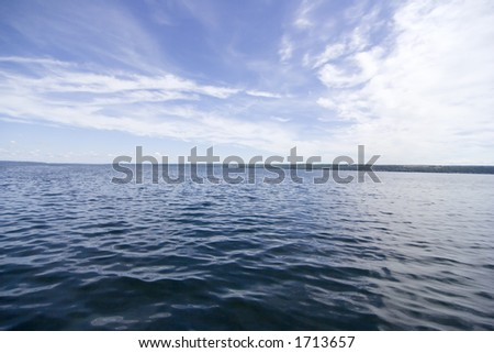Horizon of blue sky and clouds over Cayuga Lake - stock photo