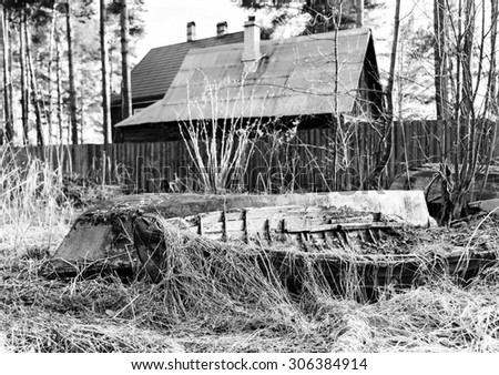 Horizontal black and white house of fisherman with old boats background