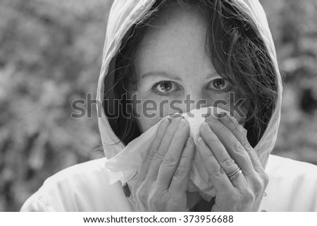 horizontal black and white image close up of a single woman outside with a hooded jacket on blowing her nose with tissues and shallow depth of field / Spring Allergies and Illness - stock photo