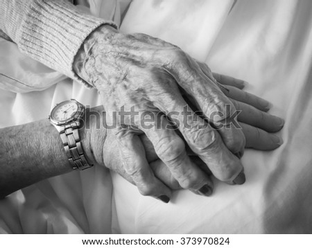 horizontal black and white image of an elderly woman's hand holding a younger woman's hand, with copy space / Comforting Hands - Black and White  - stock photo