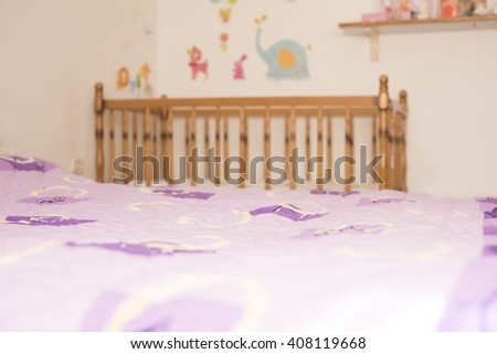 Horizontal blurred image of a baby's wooden crib in a purple and red bedroom with animal decorations on the wall and toys on a shelf - stock photo