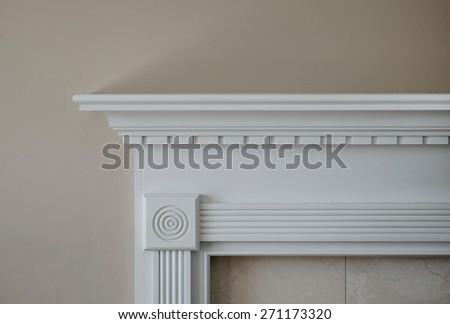 Horizontal capture of corner of white mantle and marble trim against beige wall in natural light.  - stock photo