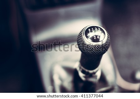 horizontal close up high angle image of a black and white manual car gear stick with the gearbox in a blurry background - stock photo