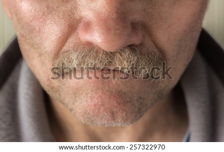 horizontal close up  image of a  caucasian man's face from the nose to bottom of chin  with mustache and facial hair. - stock photo