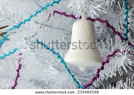 horizontal close up image of a single white ornamental christmas bell  hanging on a white christmas tree with blue and pink streamers makes for a great idea for christmas card - stock photo