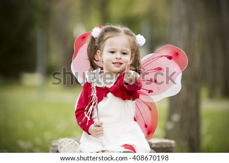 horizontal close up portrait of a little girl sitting on a park bench in spring with tongue sticking out, wearing a white dress, red blouse, with butterfly wings on her back and magic wand in her hand - stock photo