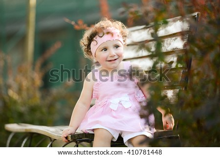 horizontal close up portrait of a little girl sitting on a wooden bench in a park, surrounded with trees on a blurry background, wearing a pink dress and hairband and smiling and looking happy - stock photo