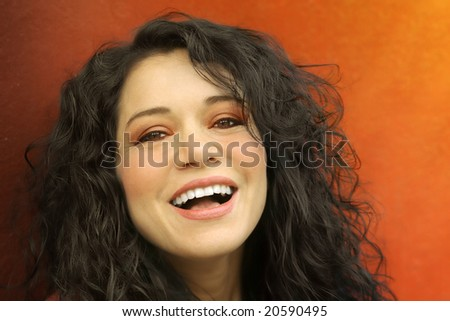 Horizontal close-up portrait of a young curly haired woman with big smile