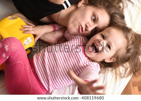 horizontal close up portrait of a young mother lying on a bed with her little daughter in pink pajamas and a yellow toy car, making faces, laughing and looking happy - stock photo