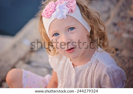 horizontal close up summer portrait of cute happy child girl sitting on sea side in pink and white headband - stock photo