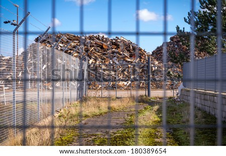 Horizontal color image of recycling centre from behind a fence. - stock photo