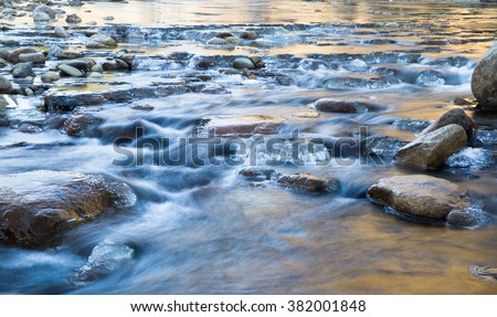 horizontal color image, taken with very slow shutter speed, showing water flowing in a creek in winter, with ice formations / Creek flowing in Winter with Rocks and Ice