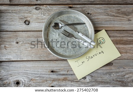 """horizontal conceptual image of an empty tin plate with cutlery and a sign saying """"i'm starving"""" on an old wood table with room for text. - stock photo"""