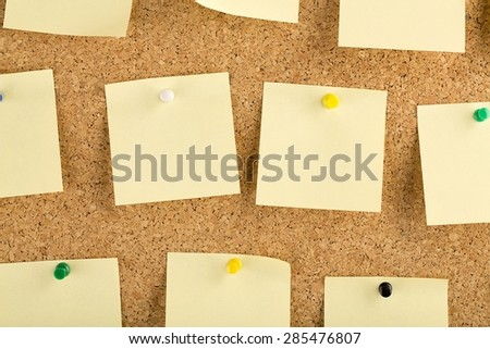 Horizontal cork board with many, yellow sticky notes pinned.