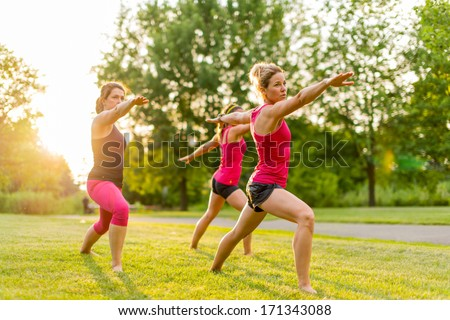 horizontal group of women doing the warrior yoga pose outdoors at sunset with lens flare - stock photo