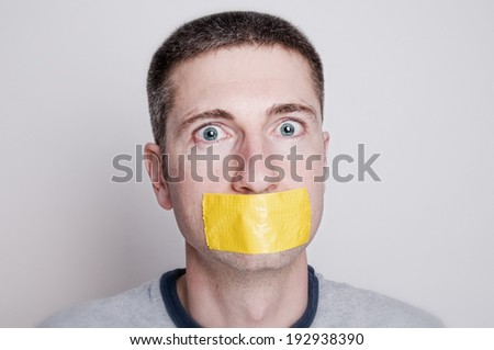 Horizontal headshot of adult man with yellow duct tape over mouth - stock photo