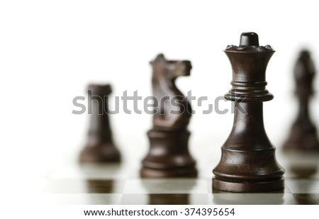 Horizontal image of a chess game with focus on the queen and a blurry pieces over white background, Copy space on the left side. Concept of corporate strategic management.. - stock photo