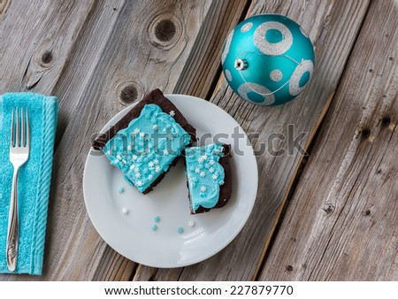 horizontal image of a chocolate brownie with blue icing on a white plate with little snow flake candy sprinkles with a fork and a blue christmas ball on a old wood board background. - stock photo
