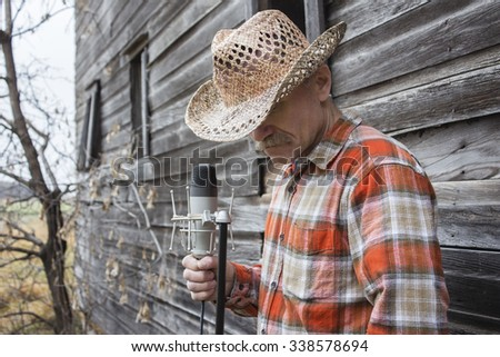 horizontal image of a cowboy singer wearing a cowboy hat and checkered western shirt standing against an old wooden exterior wall holding onto a microphone. - stock photo