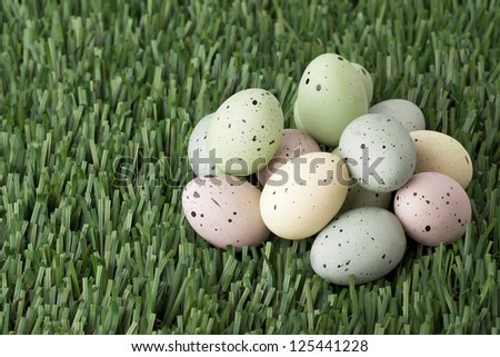 Horizontal image of a group of colorful eggs decorated with black specks laid in green grass - stock photo