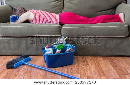 horizontal image of a house keeper sleeping on the couch with a rag in her hand and a broom and housecleaning supplies sitting on the floor next to her - stock photo