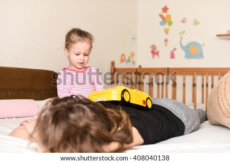 horizontal image of a little girl playing with her yellow toy car and driving it on her mother's back on the bedroom bed while her mother is sleeping - stock photo