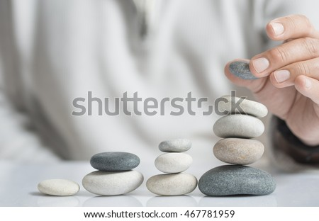 Horizontal image of a man stacking pebbles on a table with copyspace for text. Concept of risk management and wealth.