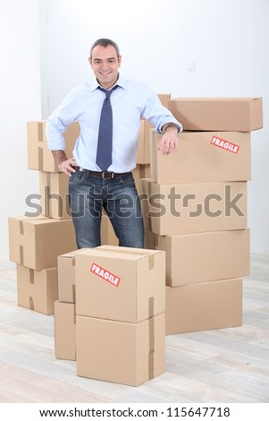 Horizontal image of a man surrounded by cardboard - stock photo