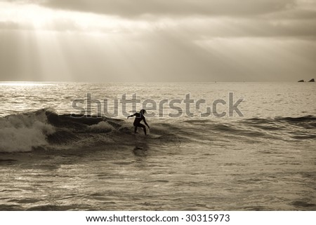 Horizontal image of a silhouette of a surfer riding a wave