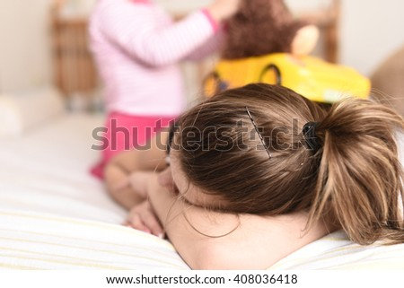 horizontal image of a young mother laying tired on the bed with her hand covering her face while her little child plays with a toy car - stock photo