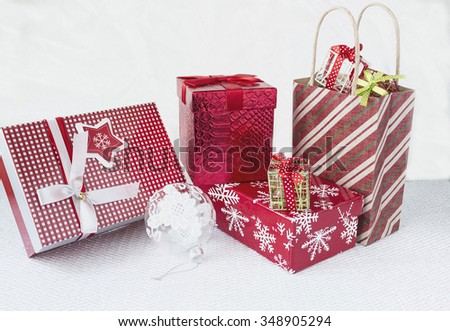 horizontal image of an assortment  of different shapes and sizes of red wrapped christmas gifts on white background - stock photo