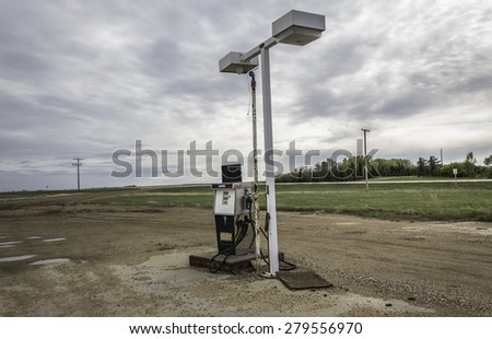 horizontal image of an old gas station pump standing under broken lights sitting next to a highway on a wet gravel surface under a rainy grey cloudy sky in the summertime - stock photo