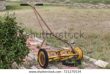horizontal image of an old vintage antique manual push mower with a broken wheel.