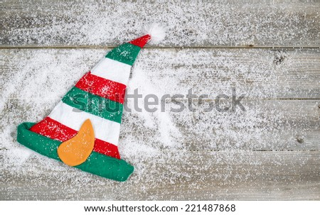 Horizontal image of Christmas elf stocking hat on rustic wooden boards covered with snow   - stock photo
