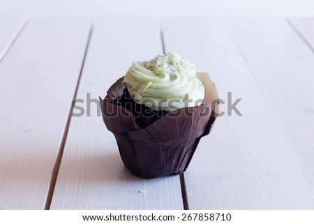 horizontal image of cupcake with green frostning on wooden background - stock photo