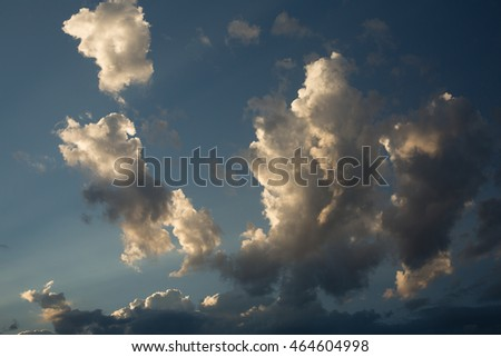 Horizontal image of early morning sun sending beams of light up into puffy clouds