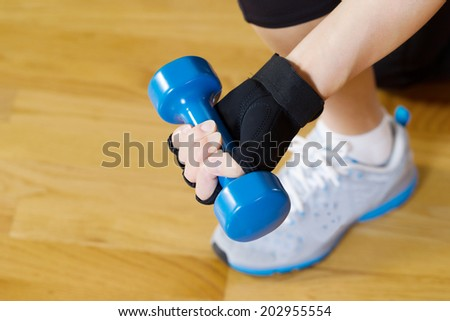 Horizontal image of female hand wearing workout glove while lifting small dumbbell weight with wooden gym floor in background   - stock photo