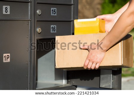 Horizontal image of female hands putting packages into postal mailbox with green grass and sidewalk in background  - stock photo