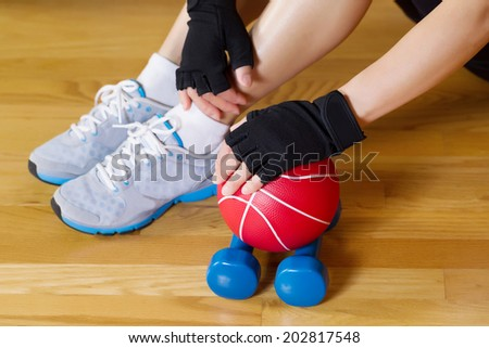 Horizontal image of female hands wearing workout gloves while resting hand on small weight ball with wooden gym floor and partial body in background  - stock photo
