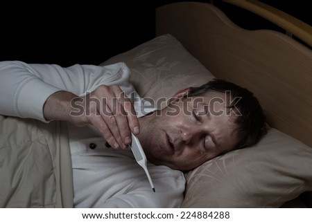Horizontal image of mature man, reading thermometer, while lying down in bed  - stock photo