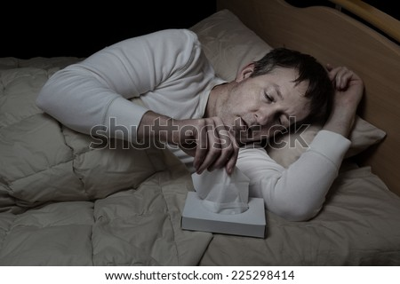 Horizontal image of sick mature man, reaching for tissue, while in bed  - stock photo