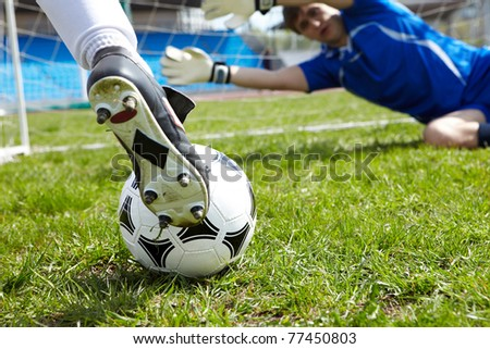 Horizontal image of soccer ball with foot of player kicking it - stock photo