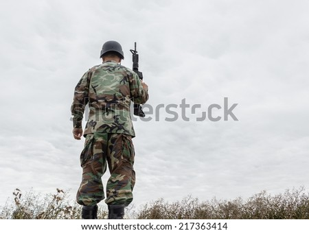 horizontal image of soldier standing at the top of  a hill with his back turned holding up his gun and looking up at the cold grey sky with a strip of dead grass at the bottom of the image . - stock photo