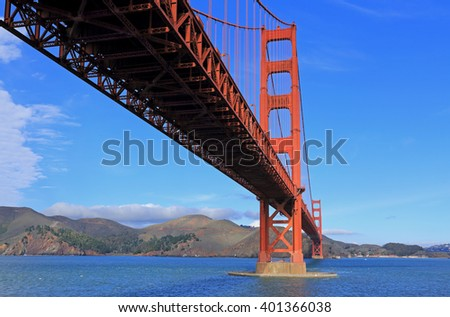 Horizontal image of the Golden Gate Bridge with blue sky, from a vantage point beneath the bridge. - stock photo
