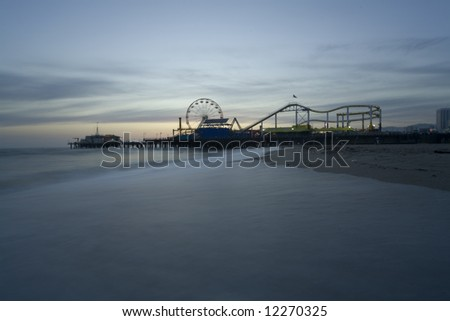 Horizontal image of the Pacific Wheel at the Santa Monica Pier amusement park.   Long exposure with misty looking waves during sunset