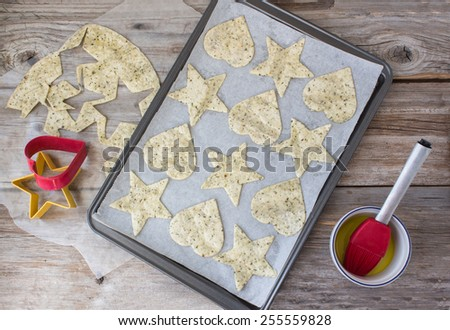 horizontal image of the process of the makings of tortilla chips made into heart and star shapes lying in cookie sheet with some left over tortilla dough and a cookie cutter on rustic wood surface. - stock photo