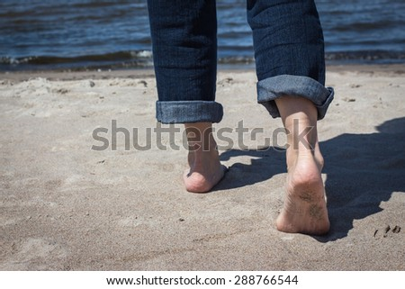 horizontal image of two feet from the knees down walking away from the camera on the beach towards the ocean