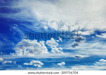 Horizontal image of white fluffy clouds on blue spring sky background. - stock photo