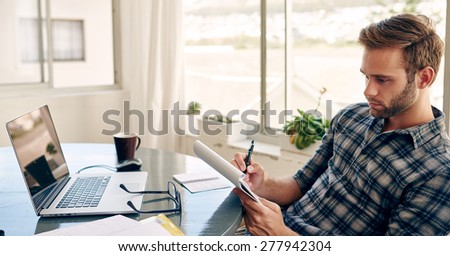 Horizontal image with copy space of a young student taking notes and working in front of his computer and morning coffee - stock photo