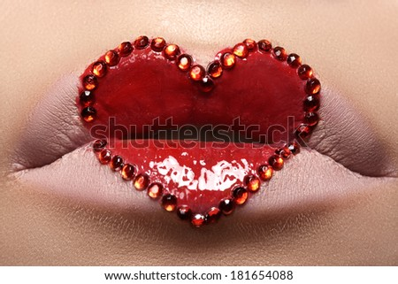 Horizontal macro of beautiful holiday lip make-up. Fashion gloss red heart lips makeup. Creative face painting. Closeup of cute Valentines day visage. Love symbol